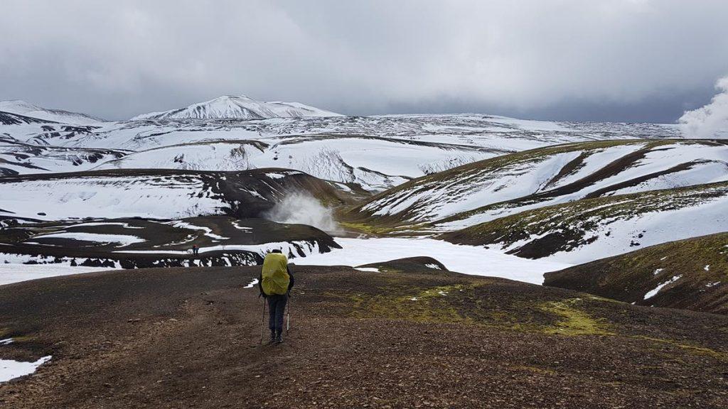 hiken met de rugzak met als uitzicht de besneeuwde heuvels in IJsland