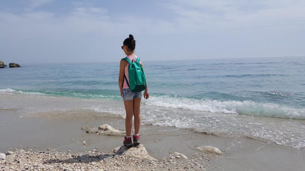 de zee in Sardinië met een tiener die op een steen staat
