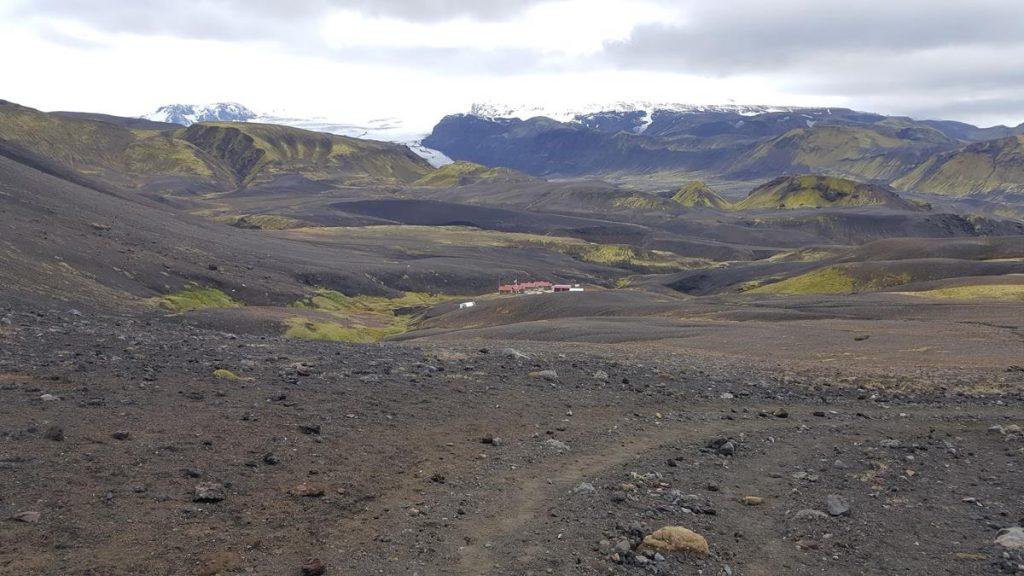 hiken in IJsland over de zwarte lavavelden en in de verte de hut van Emstrur tijdens de Laugavegur Trail