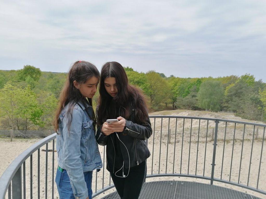 twee pubers kijken op de telefoon of de selfie goed gelukt is