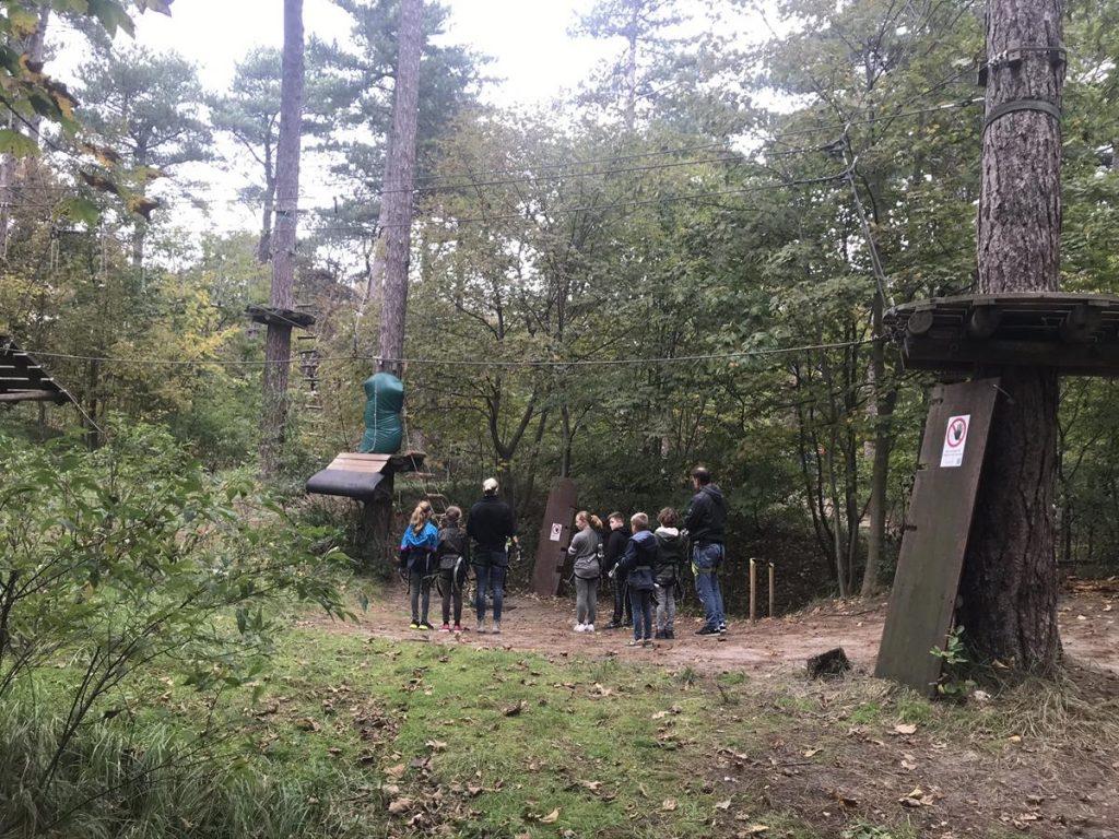 een groepje krijgt instructie bij het klimbos