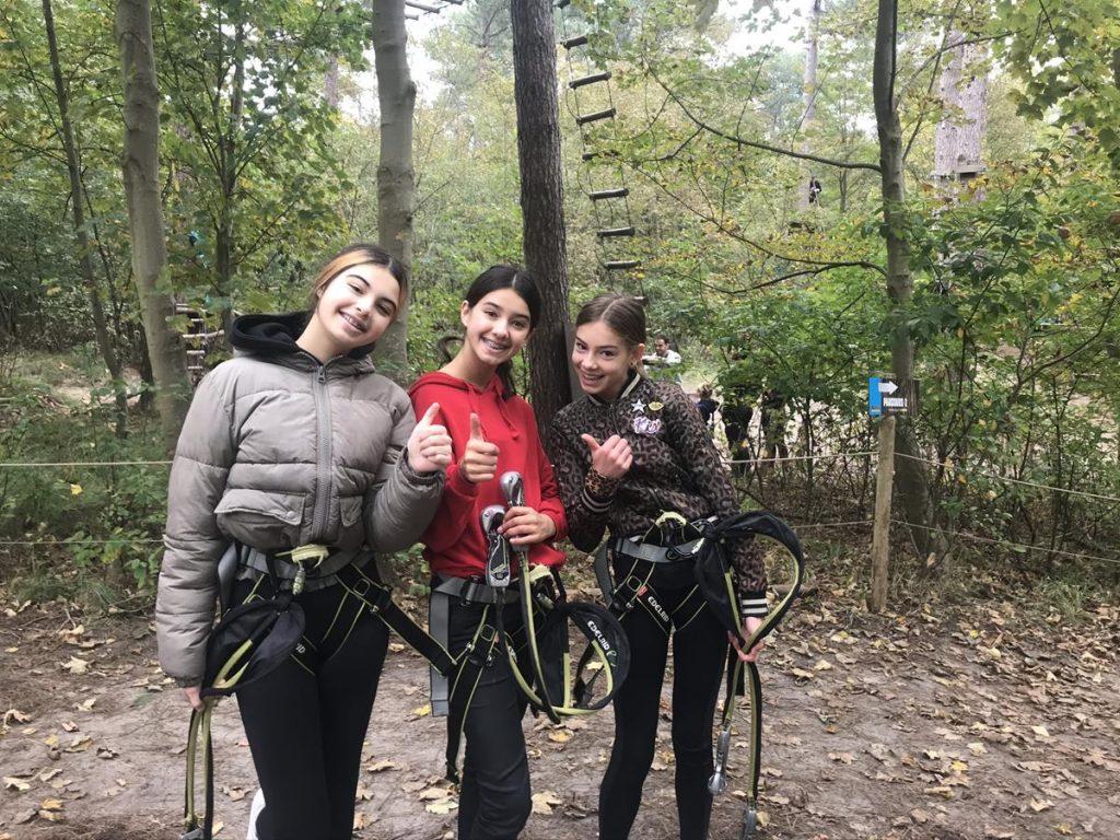 drie blije pubers nadat ze klaar waren met de parcoursen in het klimbos