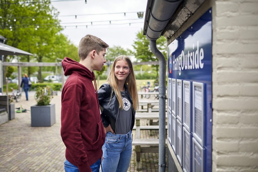 tienercampings in Nederland, twee pubers kijken op het animatiebord